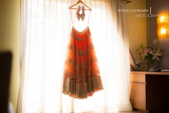 Orange Net Lehenga with Gold Motifs on a Hanger