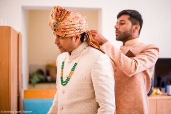 Groom wearing floral safa with brother