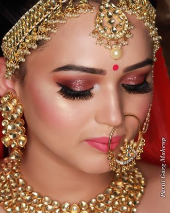 Beautiful dewy skin makeup with extended eyelashes and peach gold shimmer eyes with a lovely highlight