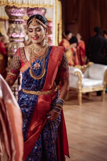 South Indian bride in a navy blue saree with red border.