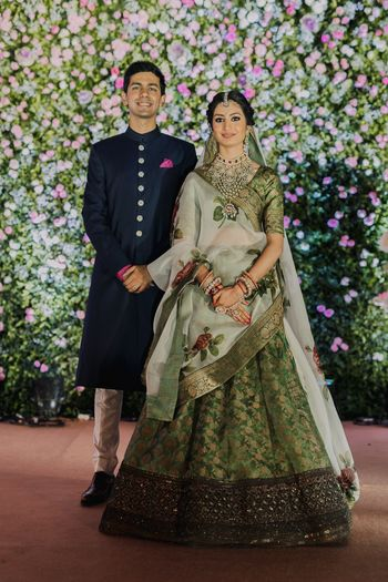 A bride in green lehenga with her groom