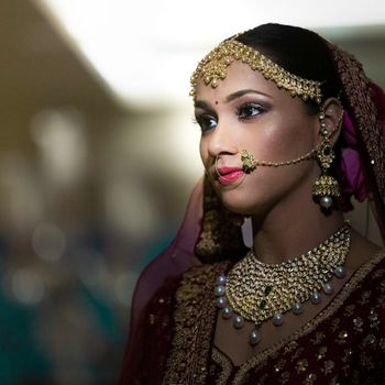 A bride in a maroon outfit and gold jewelry