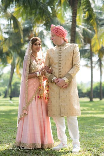 morning wedding couple with bride in light pink and groom in beige sherwani