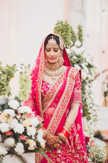 Photo of Bride in red Sabyasachi lehenga and matching jewellery