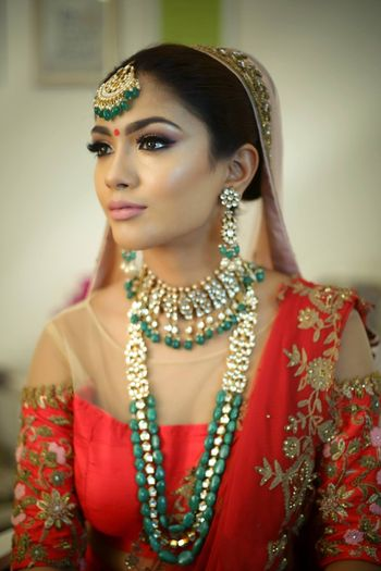 Bride with nude makeup and dark green jewellery with beads