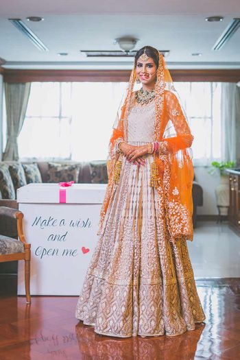 Bride in Off White Lehenga with Orange Dupatta