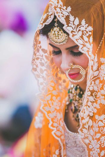 Bride in Orange Lehenga and White Embroidery and Nath