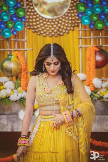 Yellow mehendi lehenga with open hair and floral jewellery