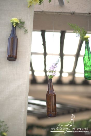 Hanging glass bottles with flowers in decor
