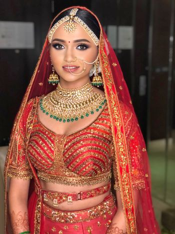Bride wearing dewy base and nude lips with her red lehenga