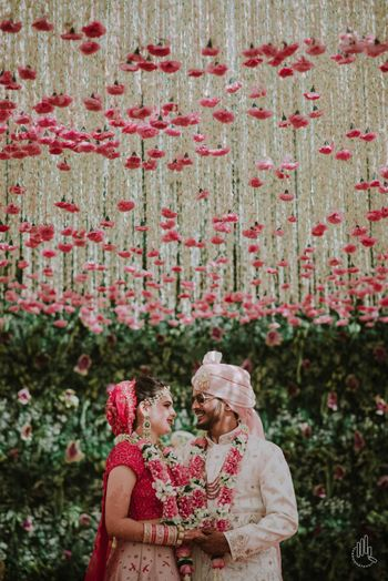 A couple stands under a ceiling made of floral ladis
