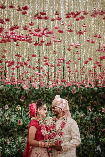 A couple poses under a floral ceiling on their wedding day