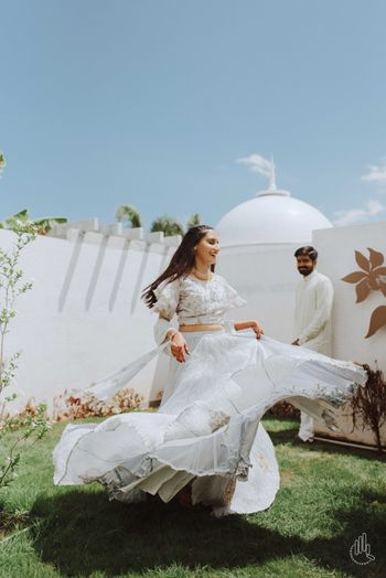 A bride twirls in a white wedding outfit during her pre wedding
