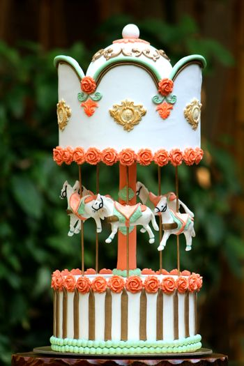 Photo of White and Gold Two Layer Cake with Horse Swings