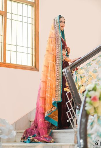 Sikh bride wearing maroon lehenga with an ombre dupatta.