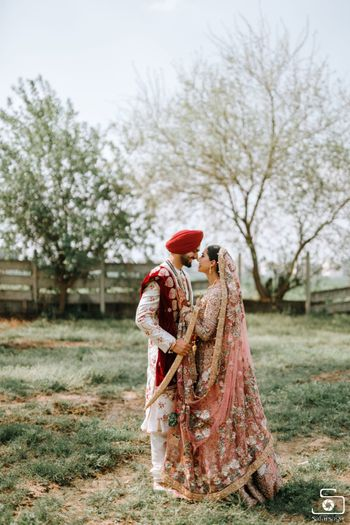 A Sikh couple posing in the fields on their wedding day.
