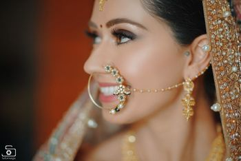 A bridal nath with floral motifs and pearls.