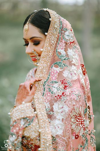 A close-up shot of a Sikh bride holding her dupatta.