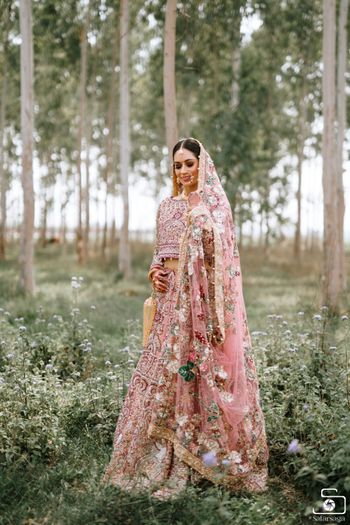 Bride wearing a fully embellished pink bridal lehenga.