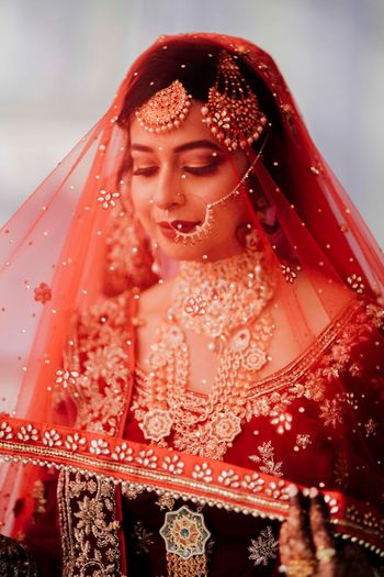 Bridal portrait using red dupatta as a veil
