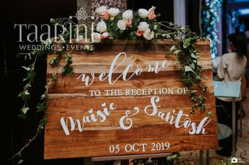 A rustic wooden signage detailed with flowers for entrance