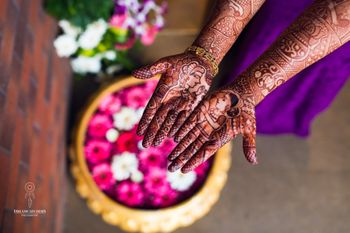 Unique bridal mehendi design with bride and groom portraits