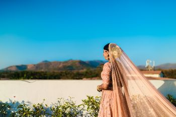 Pastel white bridal bun with peach lehenga