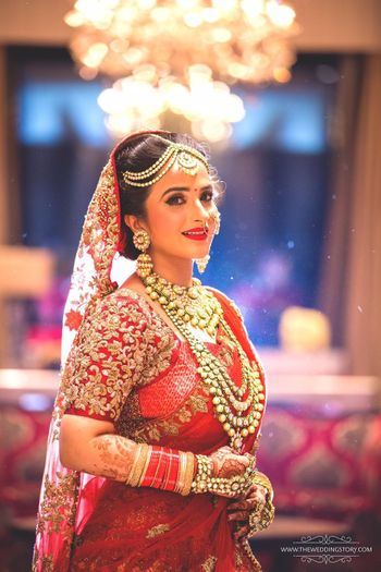 Bride in red bridal saree wearing layered jewellery