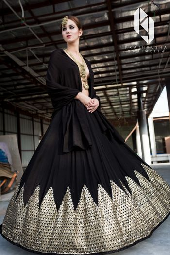 Photo of Black and gold gown for sangeet with revealing neckline