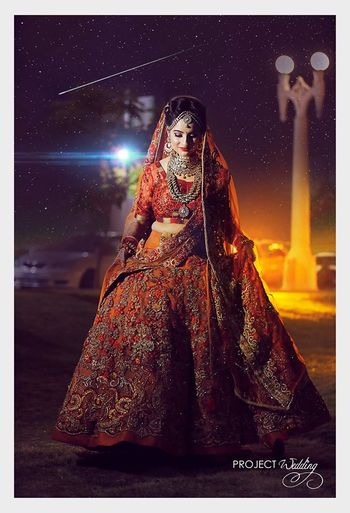 Stunning bride lifting lehenga shot
