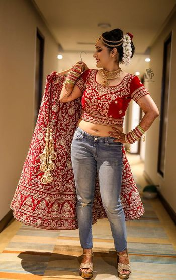 Cute bride in jeans and red lehenga