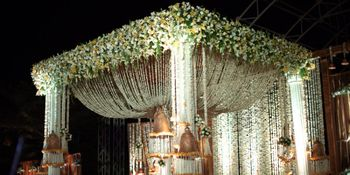 Photo of white and green flower decorated stage