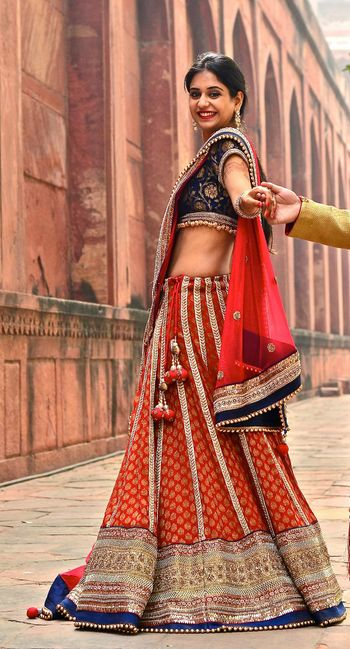 Photo of red and blue banarsi print lehenga