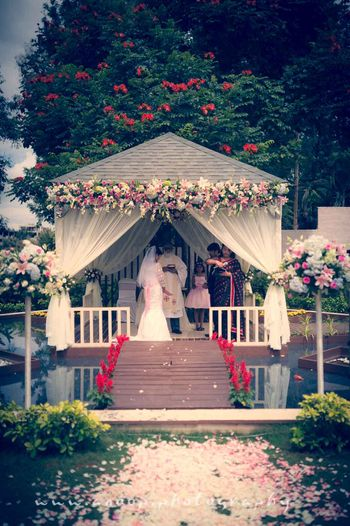 White mandap with floral arrangement and petals