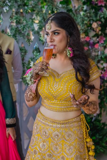 bride drinking juice on mehendi or haldi photo