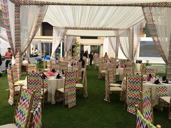 Photo of colorful stripes chairs with white theme mehendi decor