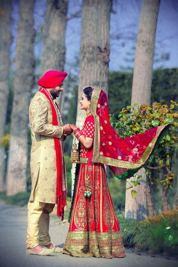 Photo of classic bridal lehenga with a twist m long red blouse with gold work
