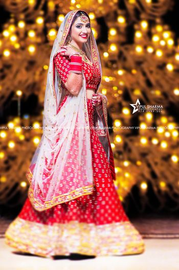Smiling bride in classic red and gold lehenga with white dupatta