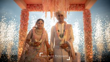 Photo of A couple stand amidst fireworks on the mandap