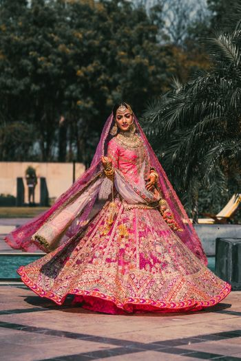 Bride twirling in heavy pink lehenga.