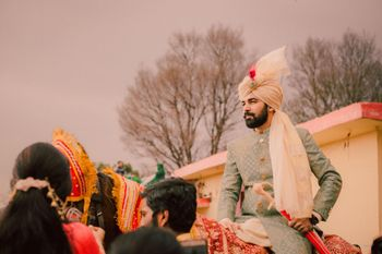 Groom in unique safa and grey sherwani entering on horse