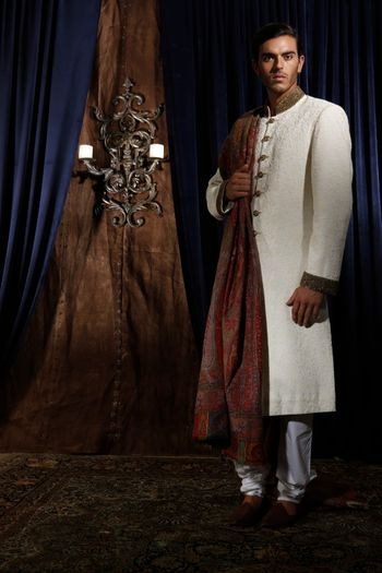 Photo of white and gold sherwani