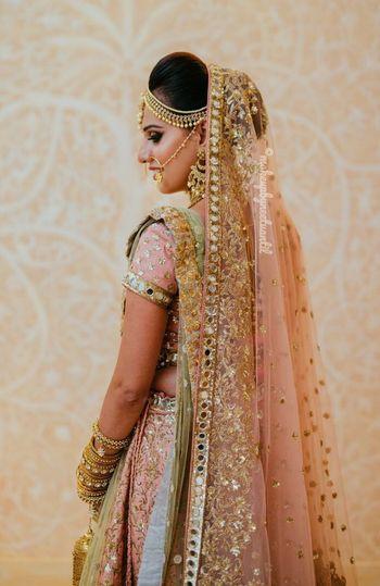 Wedding day bridal portrait in peach lehenga