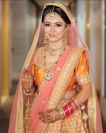 A bride in orange and pink lehenga
