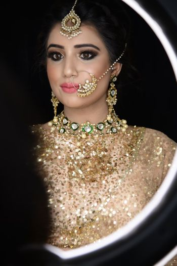 A bride wearing shimmer lehenga and dewy, nude makeup with a smokey eyeshadow