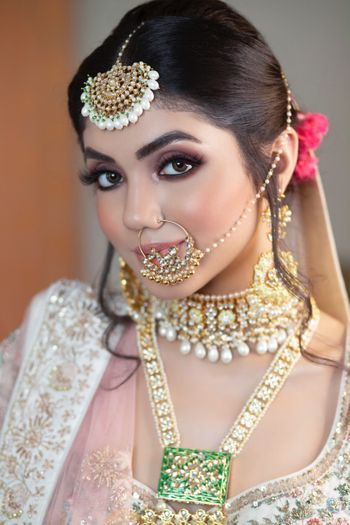 A bride in a white lehenga and subtle makeup for her wedding