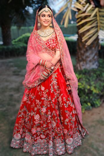 A picture of a happy bride dressed in red and pink bridal lehenga