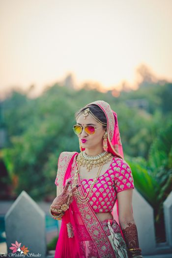 Cool bride in reflector sunglasses wearing pink lehenga