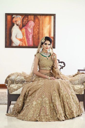 Embellished gold lehenga with contrasting green jewellery