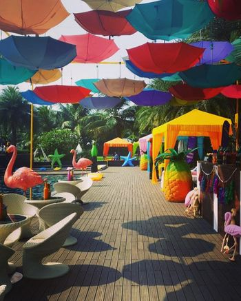 Tropical theme mehendi decor with hanging parasols